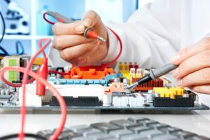 Tech testing a circuit board.